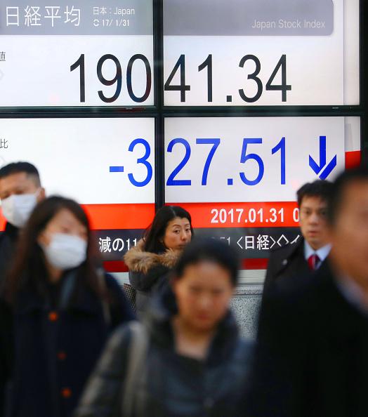 Peatones caminan frente al tablero de la Bolsa de Tokio. (Getty Images)