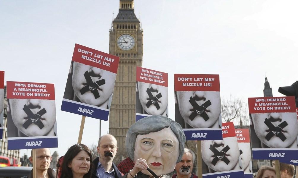 Un grupo de manifestantes utilizan una cabeza de títere de Theresa May y posan cerca del parlamento en Londres (AP)