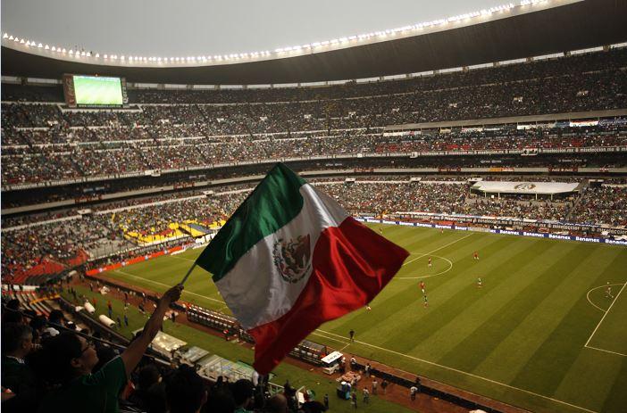 Un aficionado agita la bandera de México durante un partido de fútbol con Costa Rica en el Estadio Azteca. (AP)