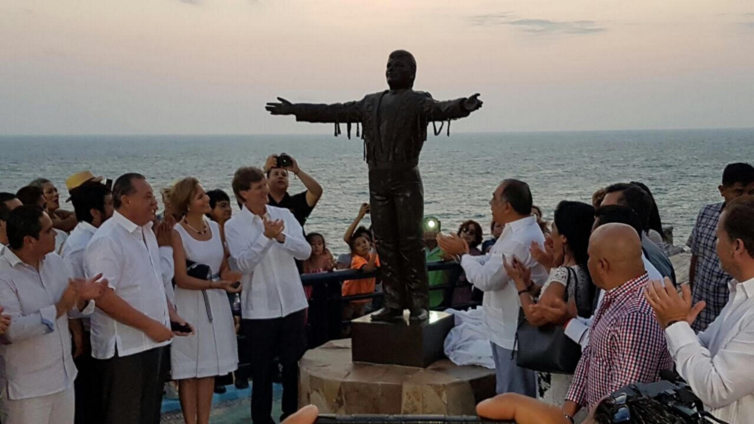personas admirando la estatua de Juan Gabriel