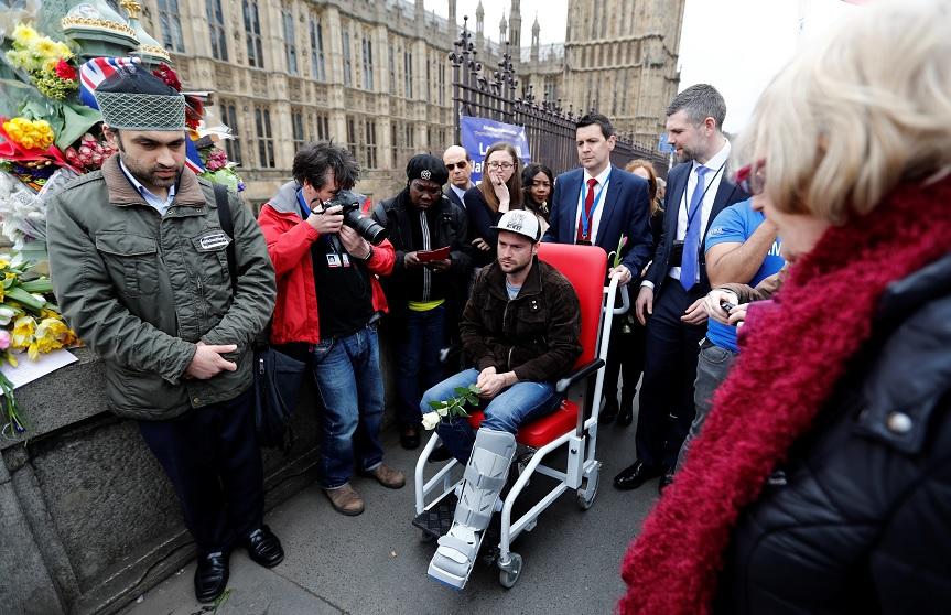 Un hombre herido sostiene una rosa en el puente de Westminster durante un homenaje a las víctimas del atentado de Londres (Reuters)