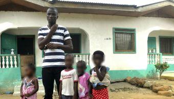 James Harris viudo de Salome Karwah y sus hijos frente a su casa de Monrovia Liberia. (AP)