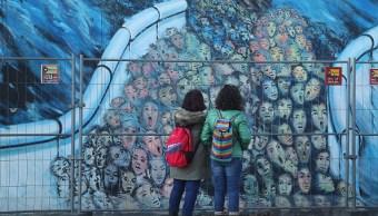 Turistas visitan el muro de Berlín, hoy cubierto por un mural- (Getty Images)