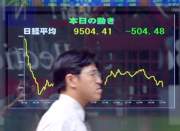 Un peatón camina frente a un tablero con información de la Bolsa de Tokio. (Getty Images, archivo)