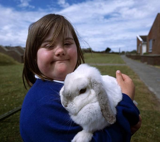 Una niña con Síndrome de Down carga a un conejo de la escuela (Getty Images)