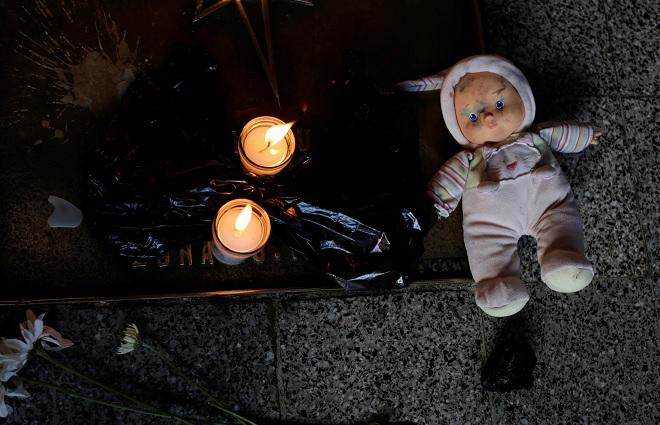 Una muñeca y velas se colocan durante una protesta para exigir justicia a las víctimas de un incendio en el refugio infantil Virgen de Asunción, frente al Palacio Nacional de Guatemala (Reuters)