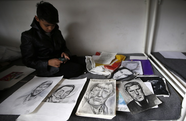 Farhad Nouri muestra los retratos de Novak Djokovic, Salvador Dali y de Angela Merkel, en su habitación en un centro de refugiados en Belgrado, Serbia (AP)
