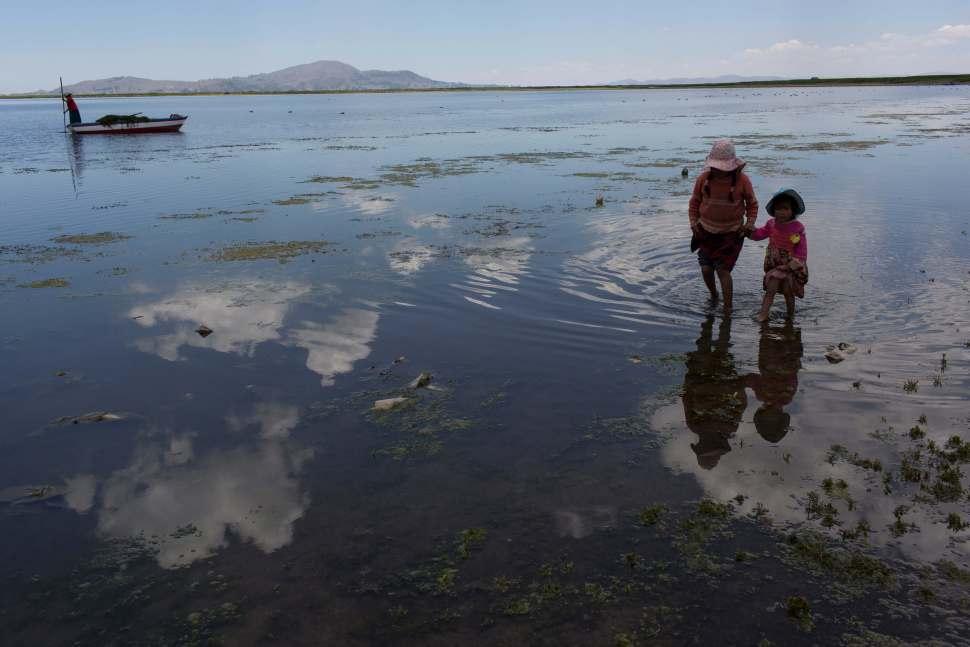 Estas personas buscan juguetes abandonados en la orilla del lago Titicaca, en Coata, Perú. Las orillas del lago están llenas de ranas muertas, cubos de pintura vacíos y bolsas de basura. (AP)