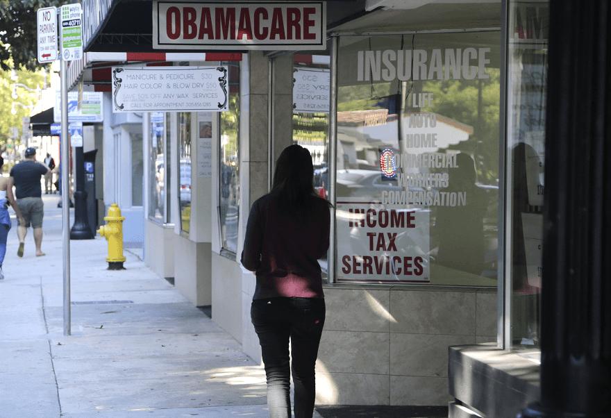 Una mujer camina, en Miami, junto a un letrero de Obamacare, como se le conoce a la reforma sanitaria de Obama. (AP, archivo)