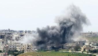Una columna de humo se levanta en el vecindario de Menshiyye tras un bombardeo por parte de las fuerzas del régimen sirio. (Getty Images/archivo)