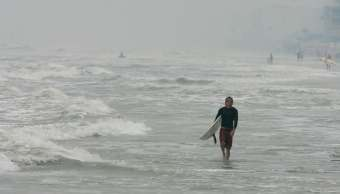 Un surfista camina a lo largo de la playa New Smyrna, en Florida. (AP/archivo)