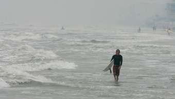Un surfista camina a lo largo de la playa New Smyrna, en Florida. (AP/archivo)