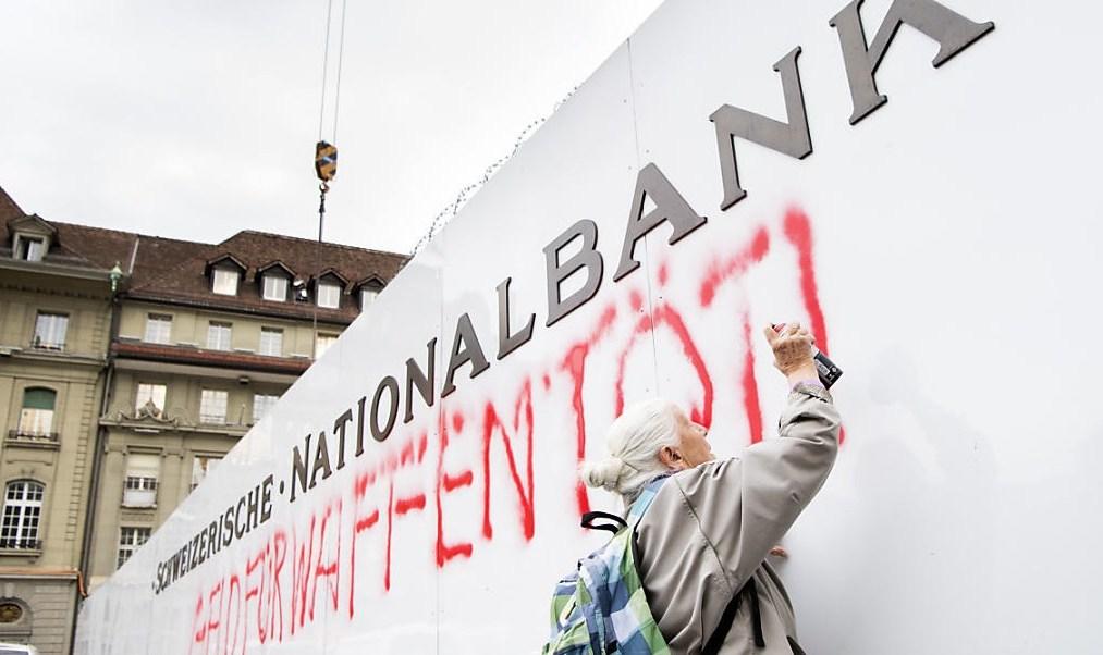"""La activista de 86 años Louise Schneider pinta el lema: """"El dinero para armas mata"""" en una pared del Banco Nacional de Suiza (Foto: luzernerzeitung.ch)"""
