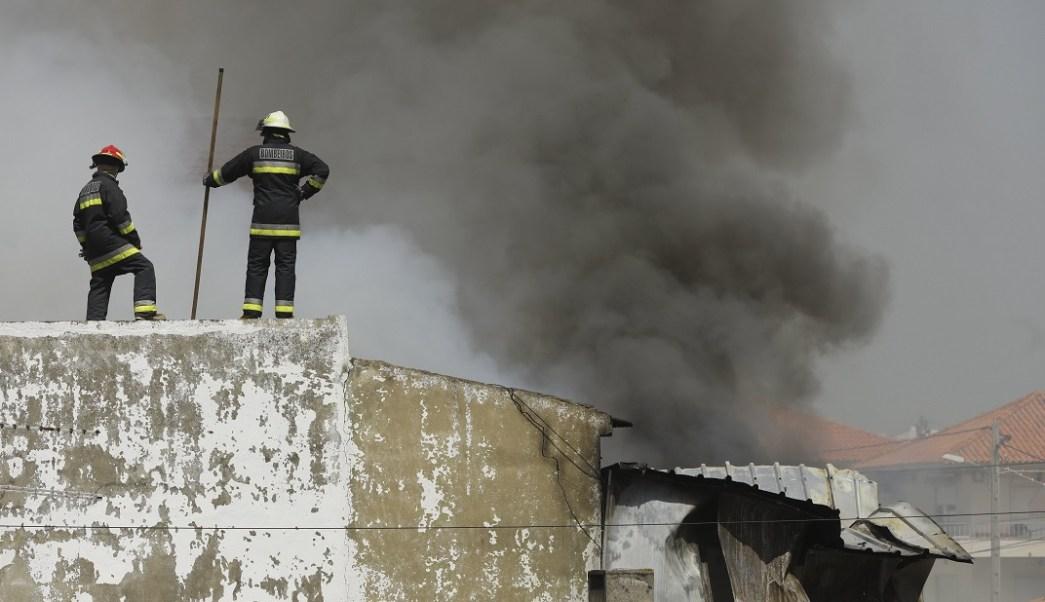 Bomberos trabajan junto a un supermercado en Tires cerca de Estoril, Portugal, tras estrellarse una avioneta (EFE)