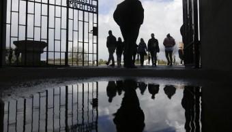 La gente entra al campo de exterminio nazi de Sachsenhausen a través de la puerta con la inscripción 'Arbeit macht frei' (el trabajo te libera) para conmemorar el 72 aniversario de la liberación del campamento en Oranienburg (AP)