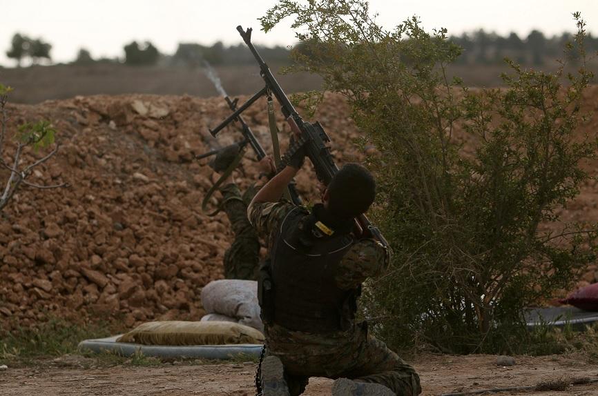 Combatientes contra el Estado Islámico en Siria disparan un arma en la orilla del río Eufrates, al oeste de la ciudad de Raqqa (Reuters)