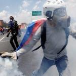 Un partidario de la oposición arroja un bote de gas lacrimógeno durante los enfrentamientos con policías en Caracas, Venezuela (Reuters)