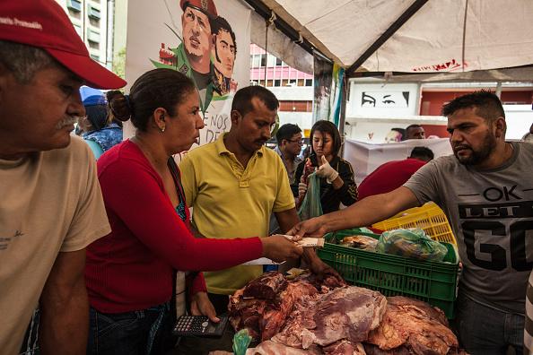 Una mujer paga por alimento en un mercado de Venezuela (Getty Images, archivo)