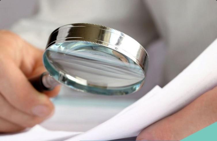 Una persona revisa documentos con una lupa; la Cofece inicia una investigación en el mercado de intermediación de títulos de deuda emitidos por el Gobierno mexicano (Twitter @cofecemx)