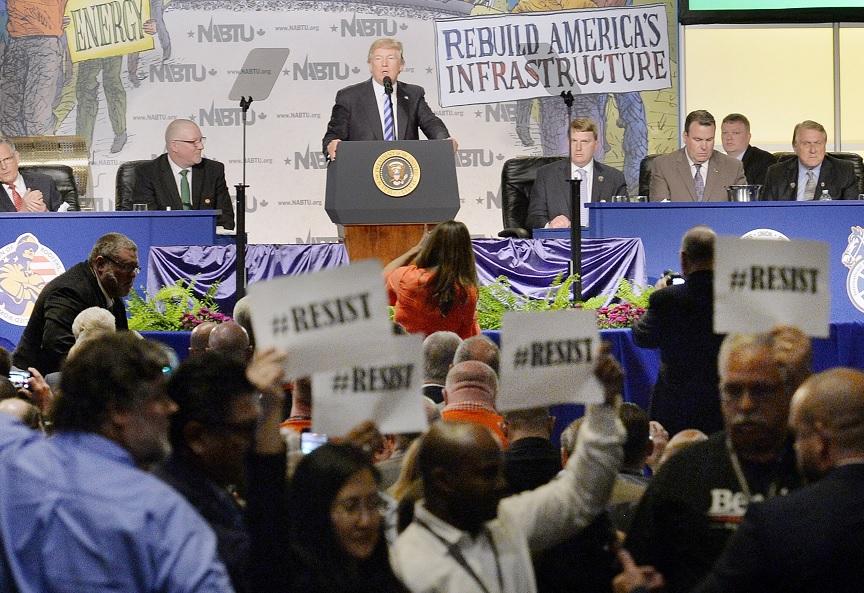 Manifestantes sostienen pancartas en las que se puede leer 'Resiste' mientras el presidente Donald Trump pronuncia un discurso en Washington (EFE)