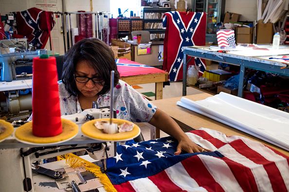 Obrera elabora una bandera de Estados Unidos; el sector manufacturero de ese país se expande durante marzo, pero en menor medida al mes anterior (Getty Images, archivo)
