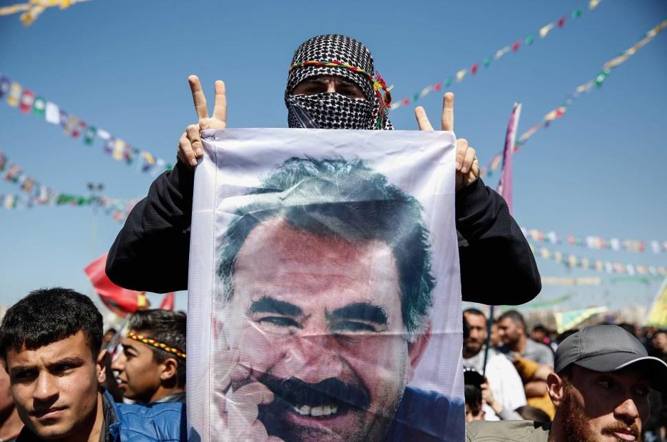 Un hombre kurdo muestra una foto de Abdullah Öcalan en manifestación.