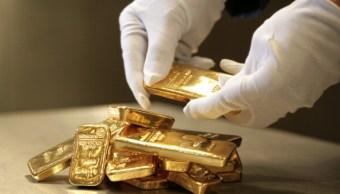 Persona apila lingotes de 500 y 1000 gramos de oro; el precio del metal desciende por fortaleza del dólar (Getty Images)