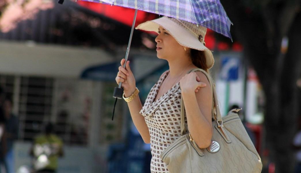 Persona se cubre del sol con sombrilla