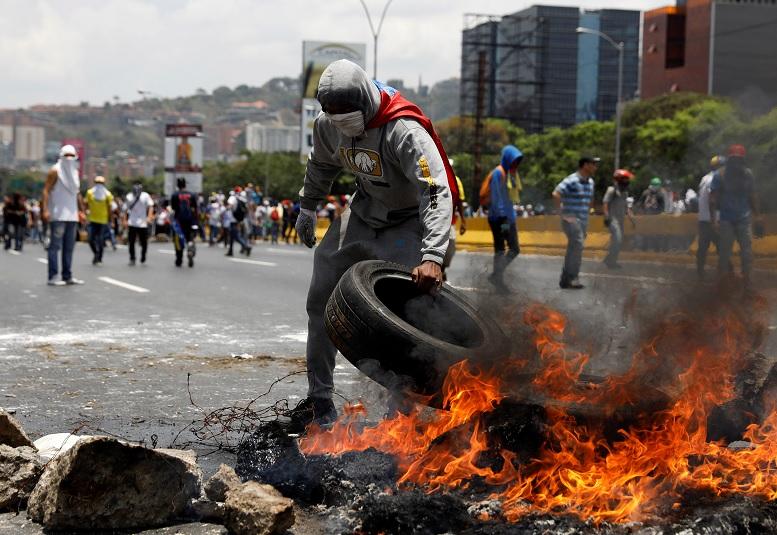 Manifestantes construyen una barricada de fuego en una calle de Caracas, Venezuela (Reuters)