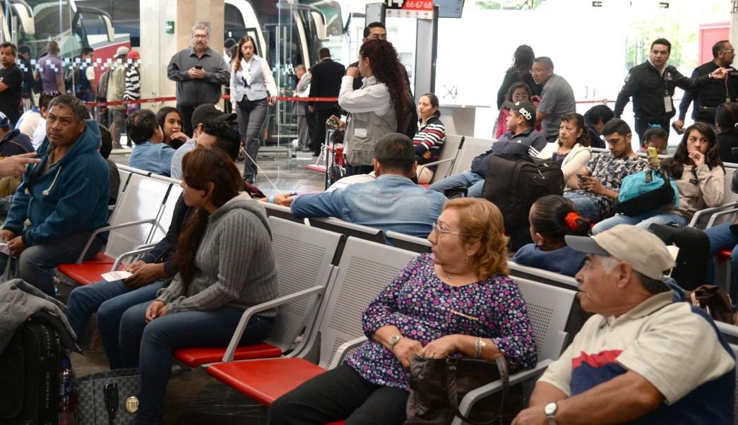 Pasajeros esperan para abordar autobús en terminal de pasajeros (NTX)