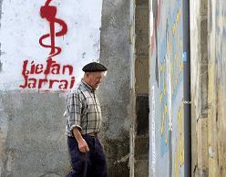 Un hombre camina frente a un graffiti que representa el logotipo del grupo separatista vasco ETA en Goizueta, España. (Reuters, archivo)