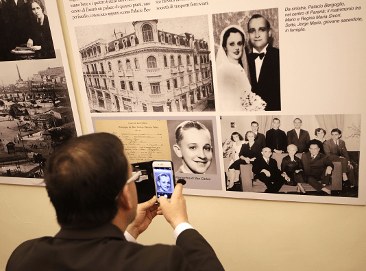 Un hombre que visita la exposición sobre la migración, en Roma, toma una foto de Jorge Bergoglio cuando era niño. (AP)