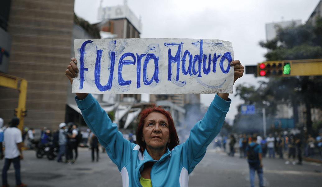 Una mujer sostiene un cartel contra el gobierno de Nicolás Maduro, en Venezuela. (AP)