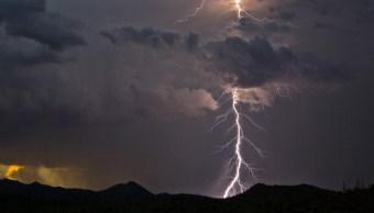 Fotografía que muestra un rayo cayendo en una zona montañosa. (Getty Images)