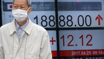 Peatón camina frente al tablero de la Bolsa de Tokio.