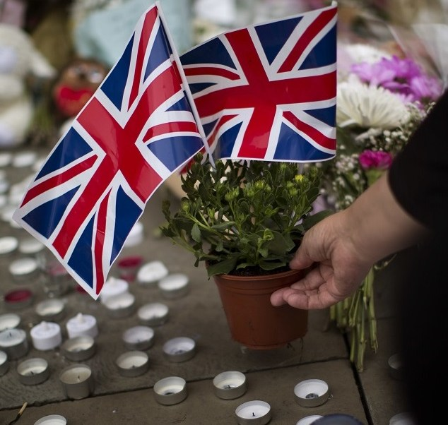 Una mujer coloca flores en Albert Square en Manchester (AP)