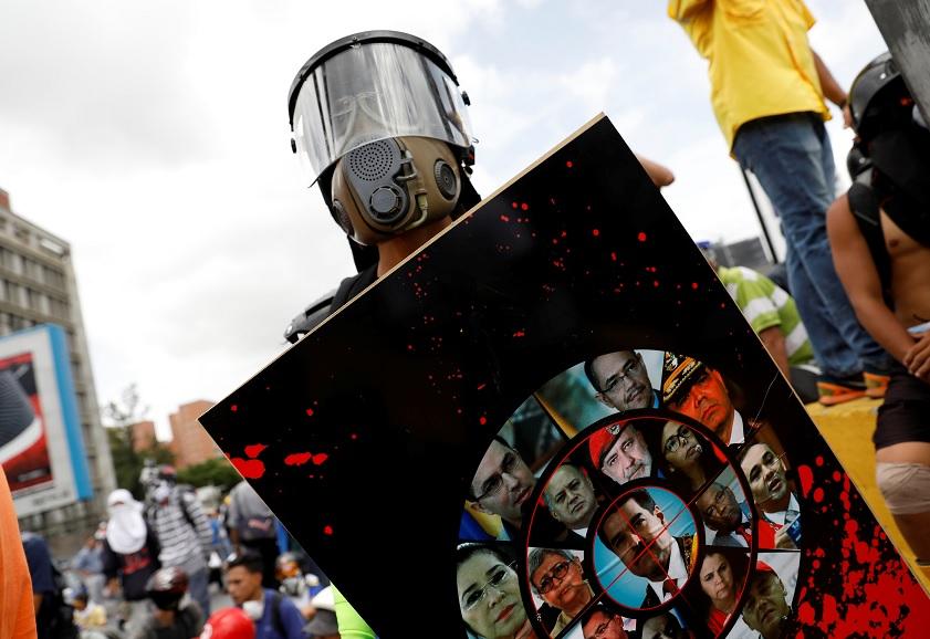 Un manifestante usa un escudo hecho con fotos de políticos de Venezuela (Reuters)