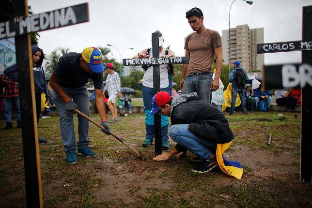 Manifestantes colocan cruces con los nombres de las personas que han muerto durante las protestas de la oposición en Caracas, Venezuela. (AP)