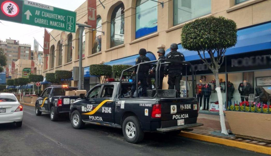 Dos patrullas de la SSP-CDMX vigilan el exterior de una plaza comercial. (SSP-CDMX)