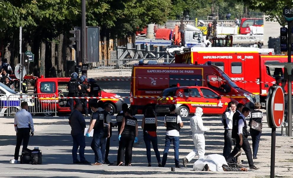 La policía inspecciona el cadáver de un hombre que impacto su automóvil con una camioneta de la gendarmería en la avenida de los Campos Elíseos en París (Reuters)