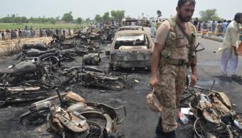 Un soldado pakistaní resguarda vehículos quemados en la escena de un accidente las afueras de Bahawalpur, Pakistán (EFE)