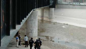 Policías rodean el cuerpo de Adrián Hernández, baleado en la frontera