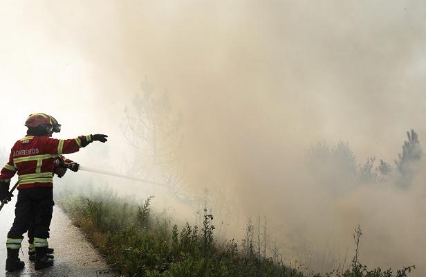 Bomberos trabajan para extinguir un incendio en un bosque cerca de Cadafaz, Portugal (EFE)
