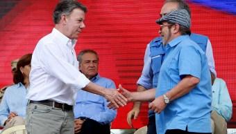"""El presidente de Colombia, Juan Manuel Santos, estrecha la mano del máximo líder de las FARC, Rodrigo Londoño, """"Timochenko"""" (EFE)"""