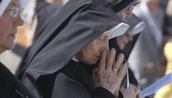 Una monja ora durante una procesión por el Jueves de Corpus Christi