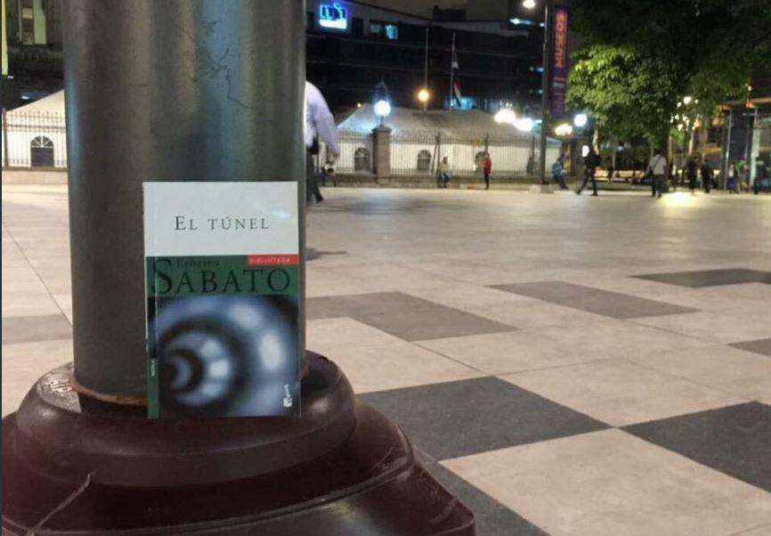 Una persona siembra un libro en una plaza publica