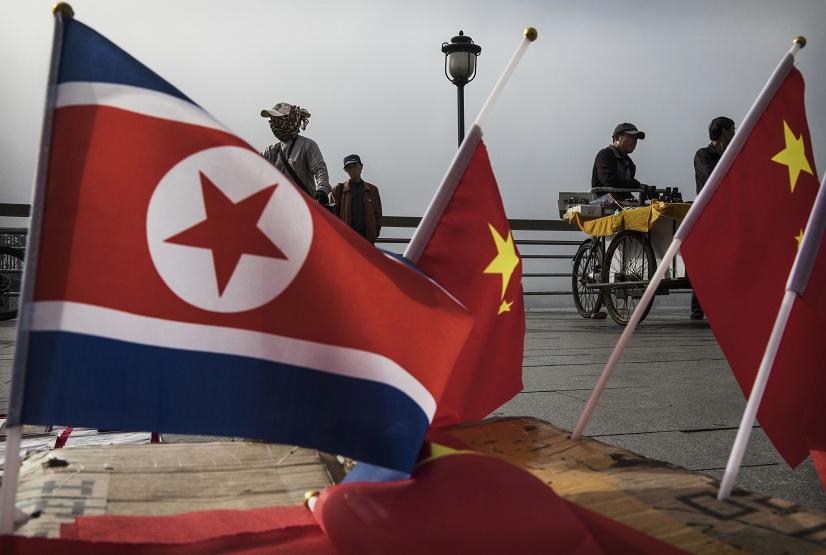 Vendedores con banderas de Corea del Norte y China en el paso junto al río Yalu en la ciudad fronteriza de Dandong (Getty Images)