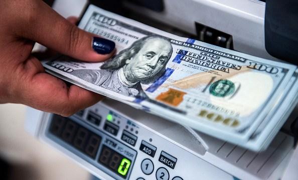 Billetes de 100 dólares en máquina de contar dinero