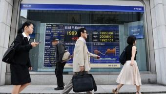 Peatones frente al tablero electrónico de la Bolsa de Tokio