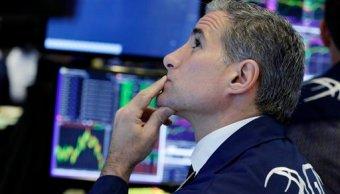 Especialista trabaja en la sala de transacciones en Bolsa de NY